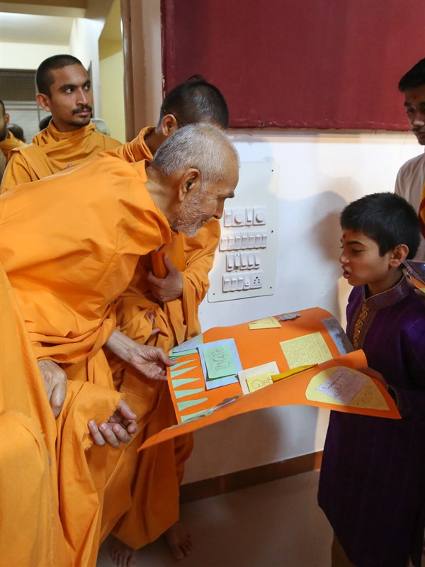 Swamishri observes a card prepared by a child
