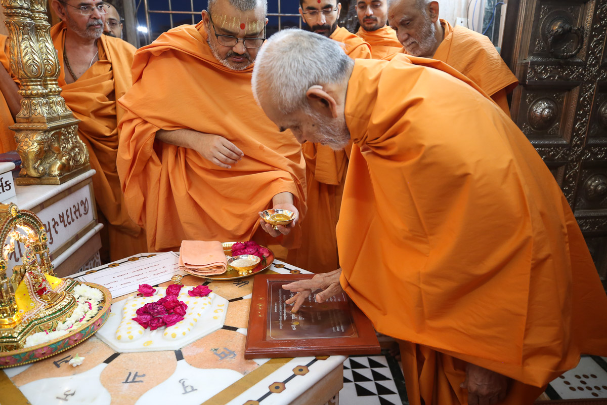 Swamishri performs pujan of a plaque engraved with the new Swaminarayan Ashray Dikshamantra