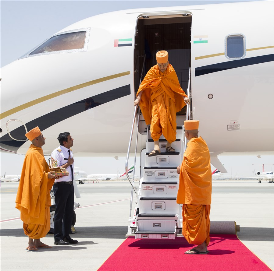 Param Pujya Mahant Swami Maharaj descends from the plane at DWC Airport