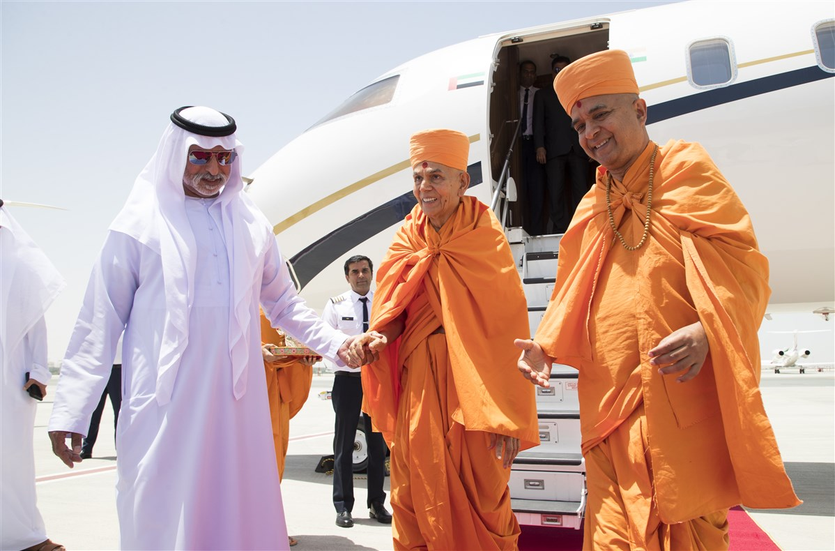 HE Sheikh Nahyan Mabarak Al Nahyan leads Swamishri towards the airport terminal