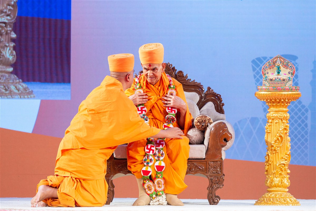 Brahmavihari Swami welcomes Swamishri with a garland