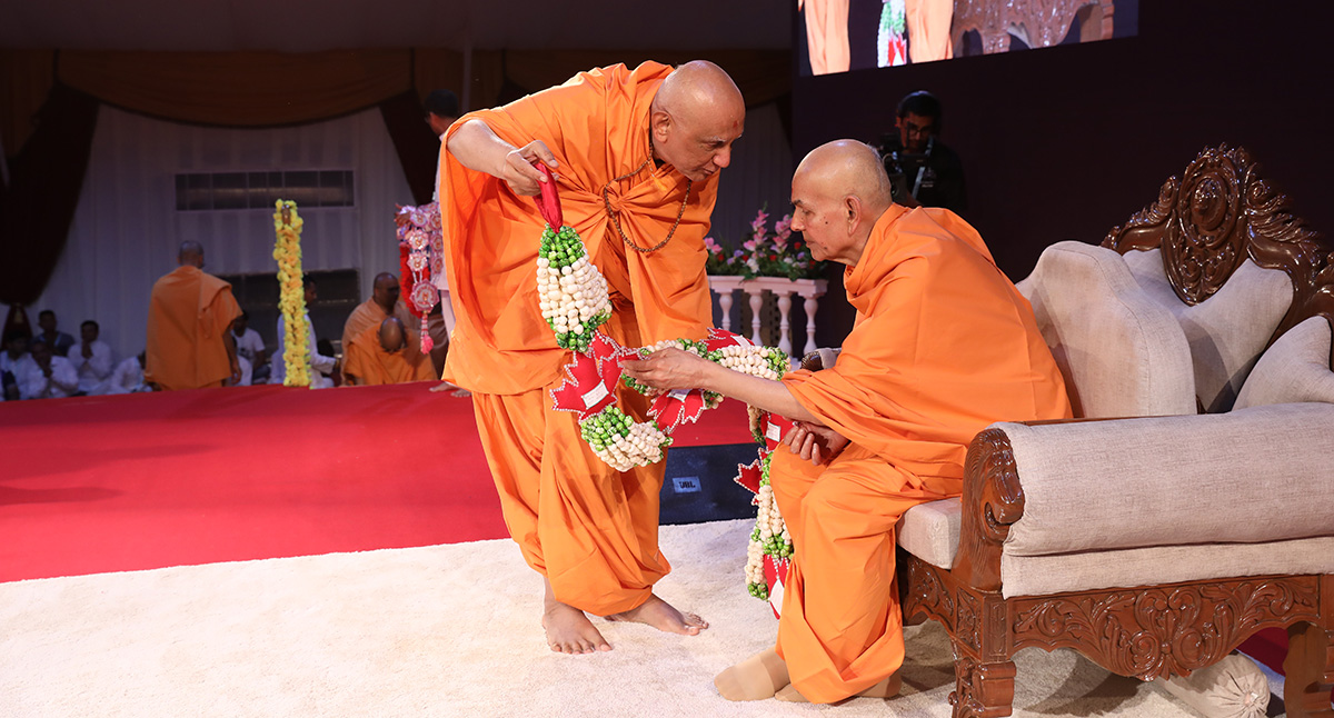 Swamishri observes a garland of puffed fox nuts (makhana)