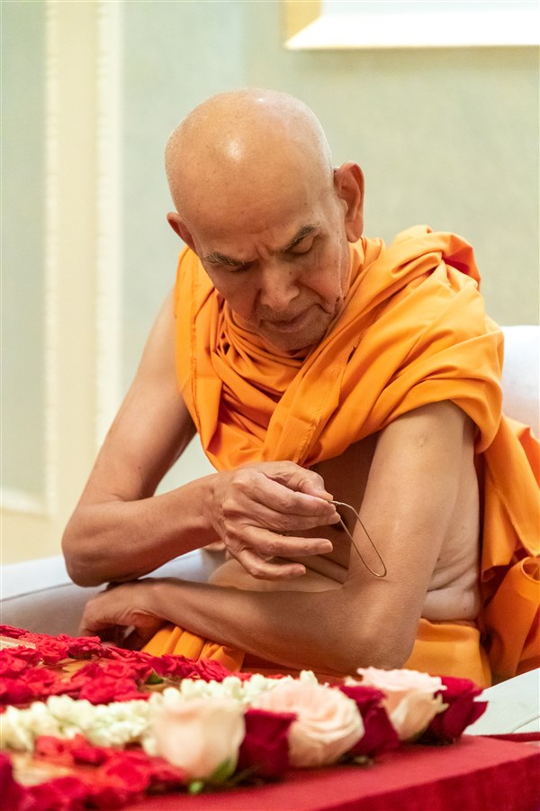 Swamishri applies tilak on his upper arm