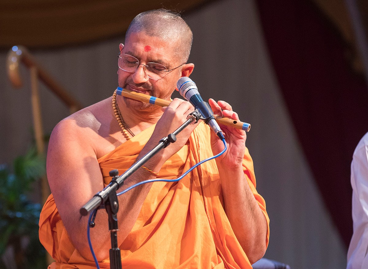 A swami plays the flute in the kirtan aradhana