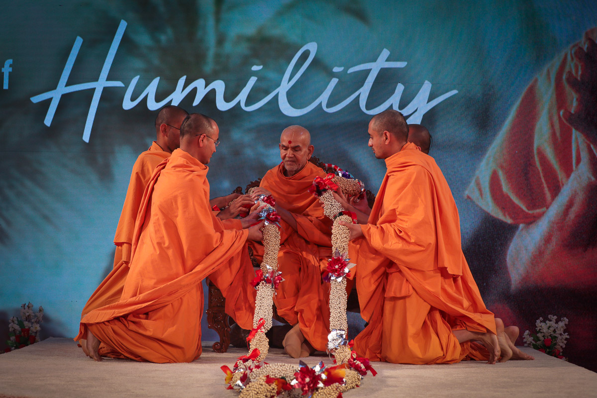 Sadhus honor Swamishri with a garland