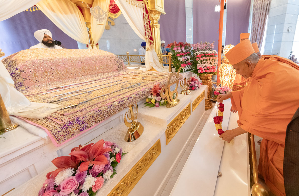 Swamishri places a garland to honor the Guru Granth Sahib