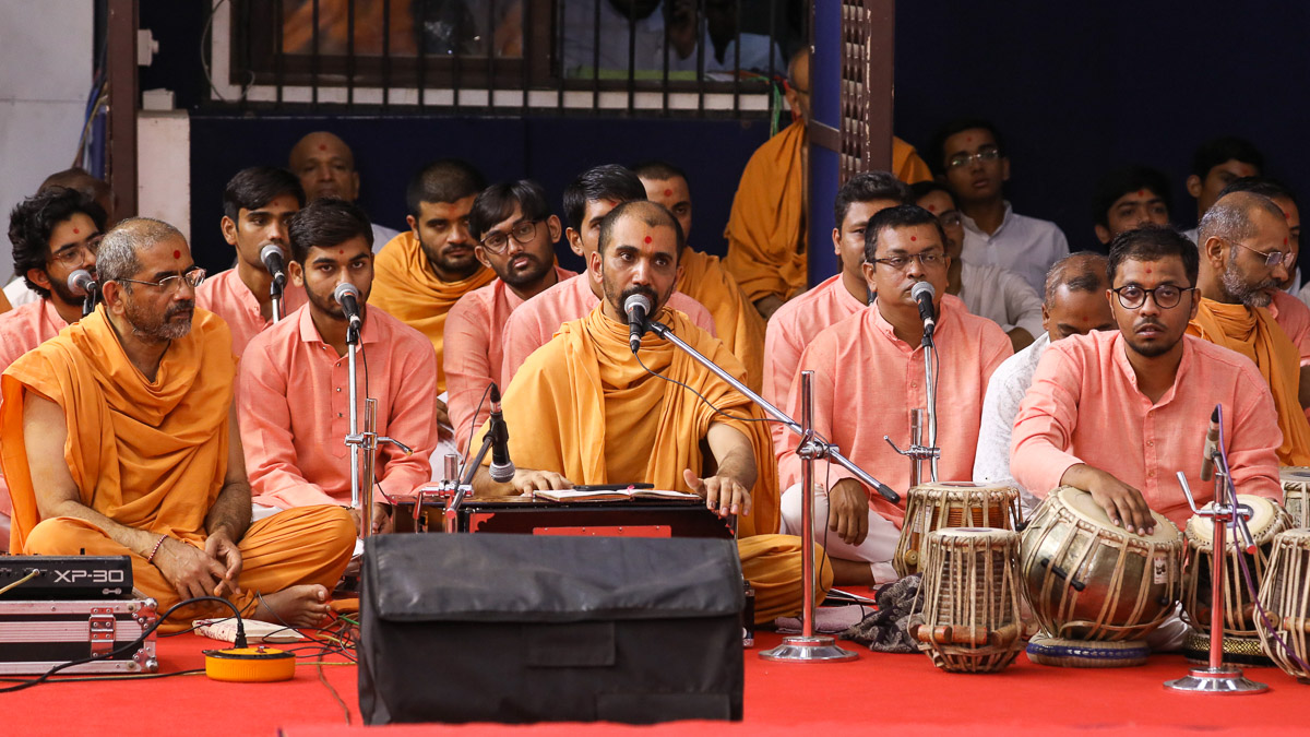 Sadhus and youths sing kirtans in Swamishri's morning puja