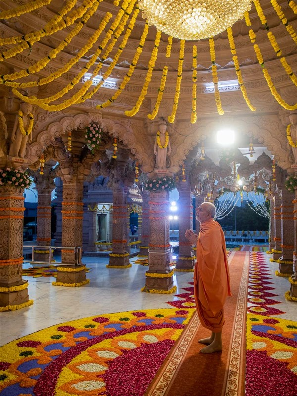 Swamishri observes the flower decorations under the mandir dome