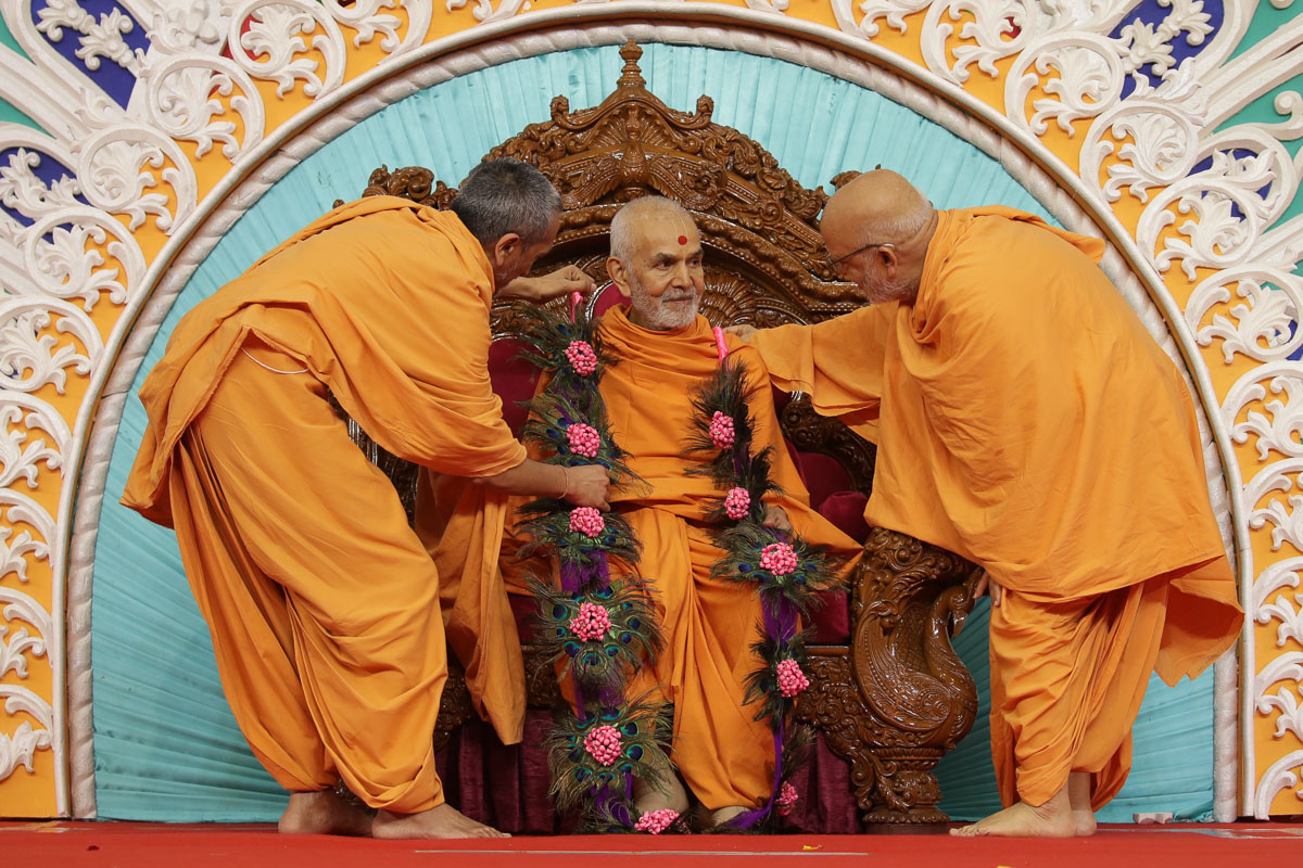 Pujya Ghanshyamcharan Swami and Uttamprakash Swami honor Swamishri with a garland