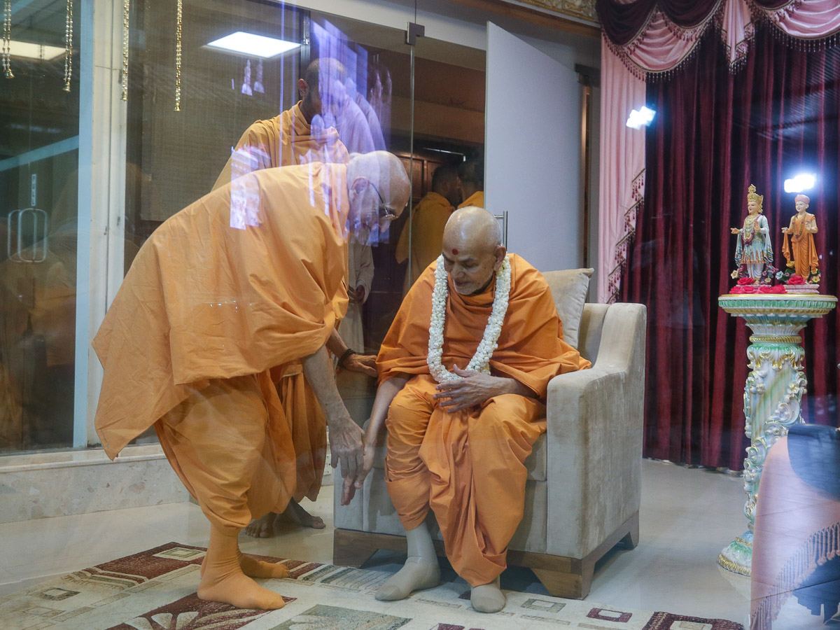 Ramcharan Swami welcomes Swamishri with a garland