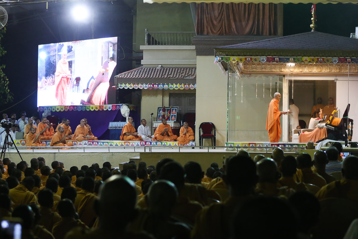 Swamishri performs the evening arti in the Pramukh Mandiram during the Sunday satsang assembly