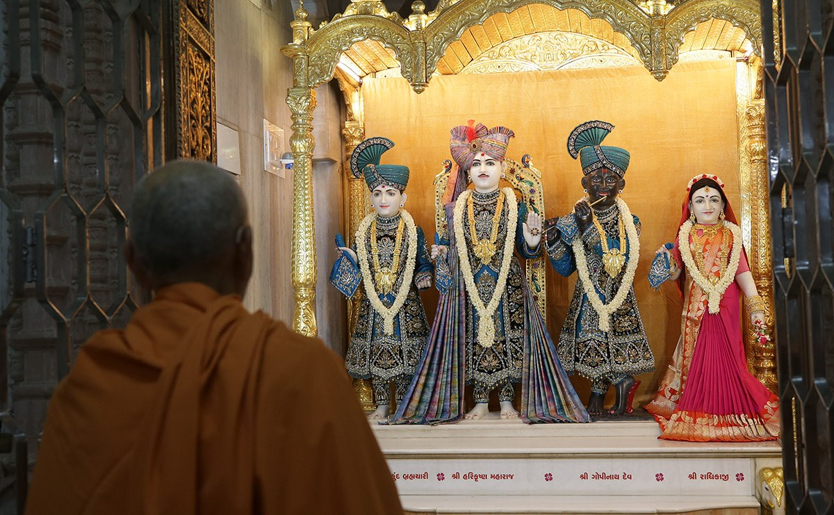 Swamishri engrossed in the darshan of Shri Varninath Maharaj and Shri Gopinath Dev