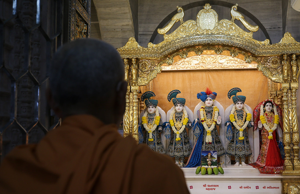 Swamishri engrossed in the darshan of Shri Dharmakul