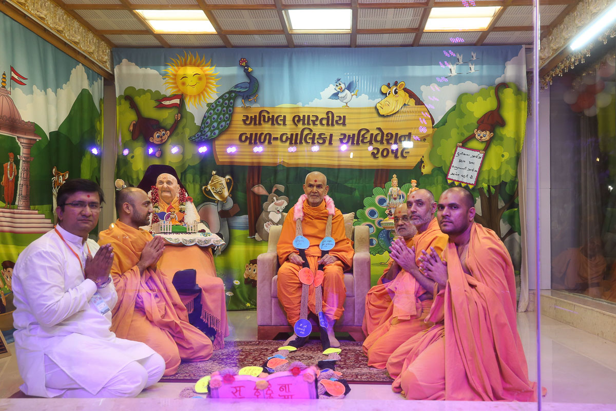Sadhus and volunteers of the Bal Pravrutti Madhyastha Karayalay honor Swamishri with a garland