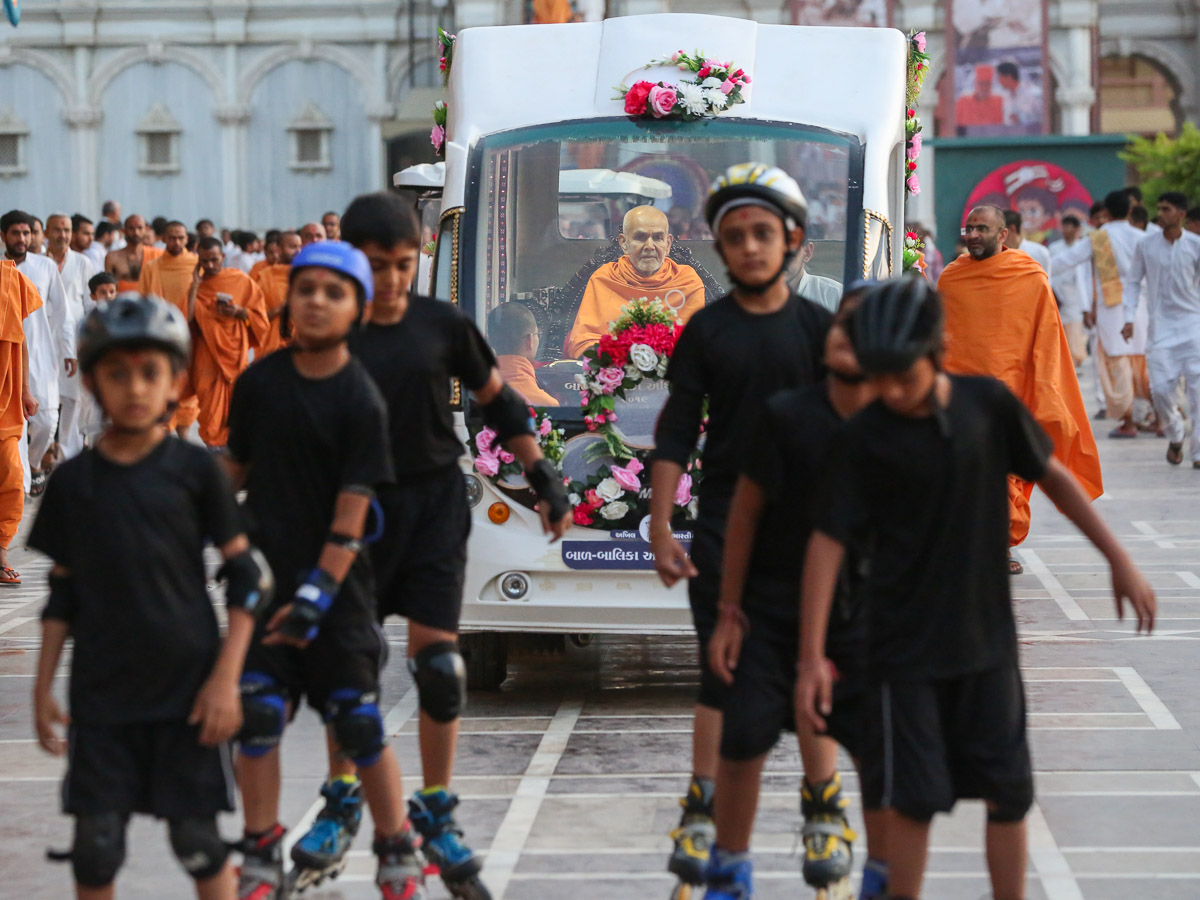Children lead Swamishri to the assembly hall