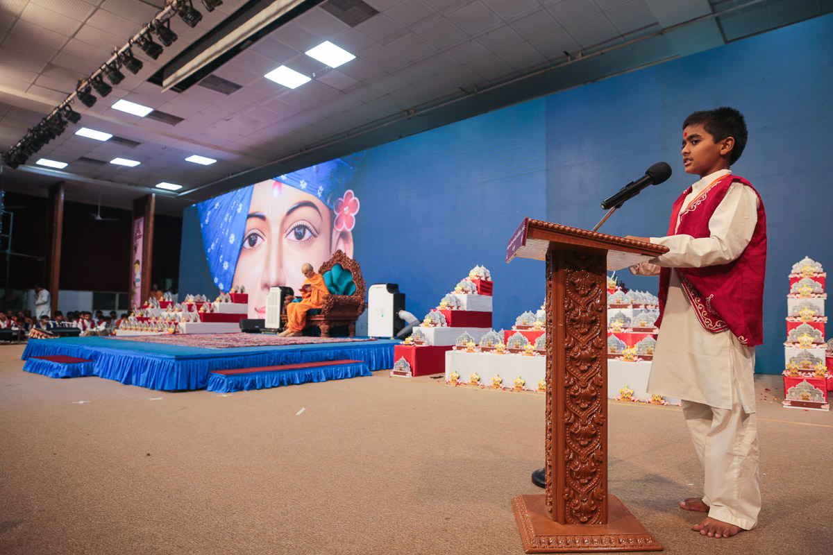 A child presents during Swamishri's puja