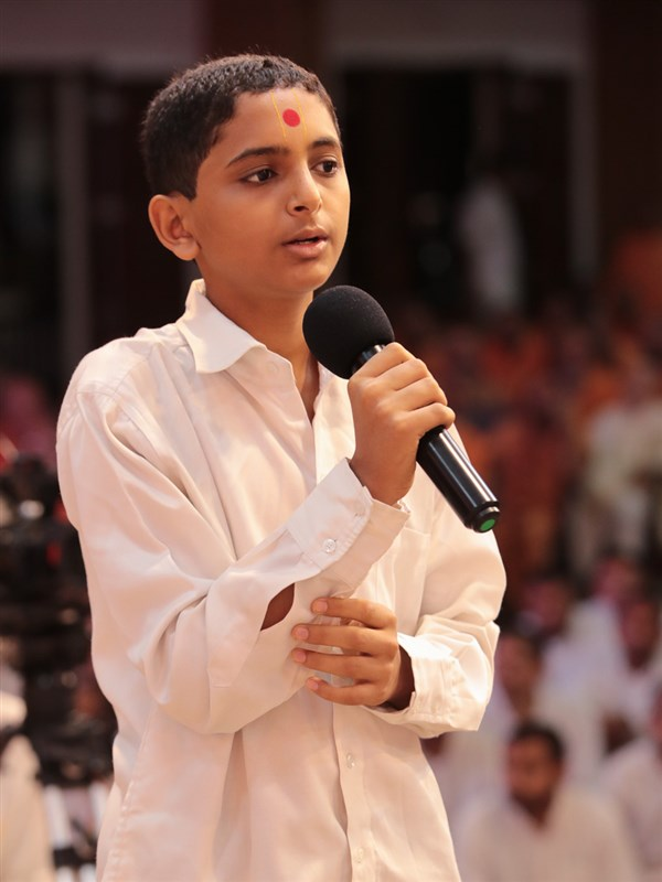 A youth recites scriptural passages in Swamishri's puja