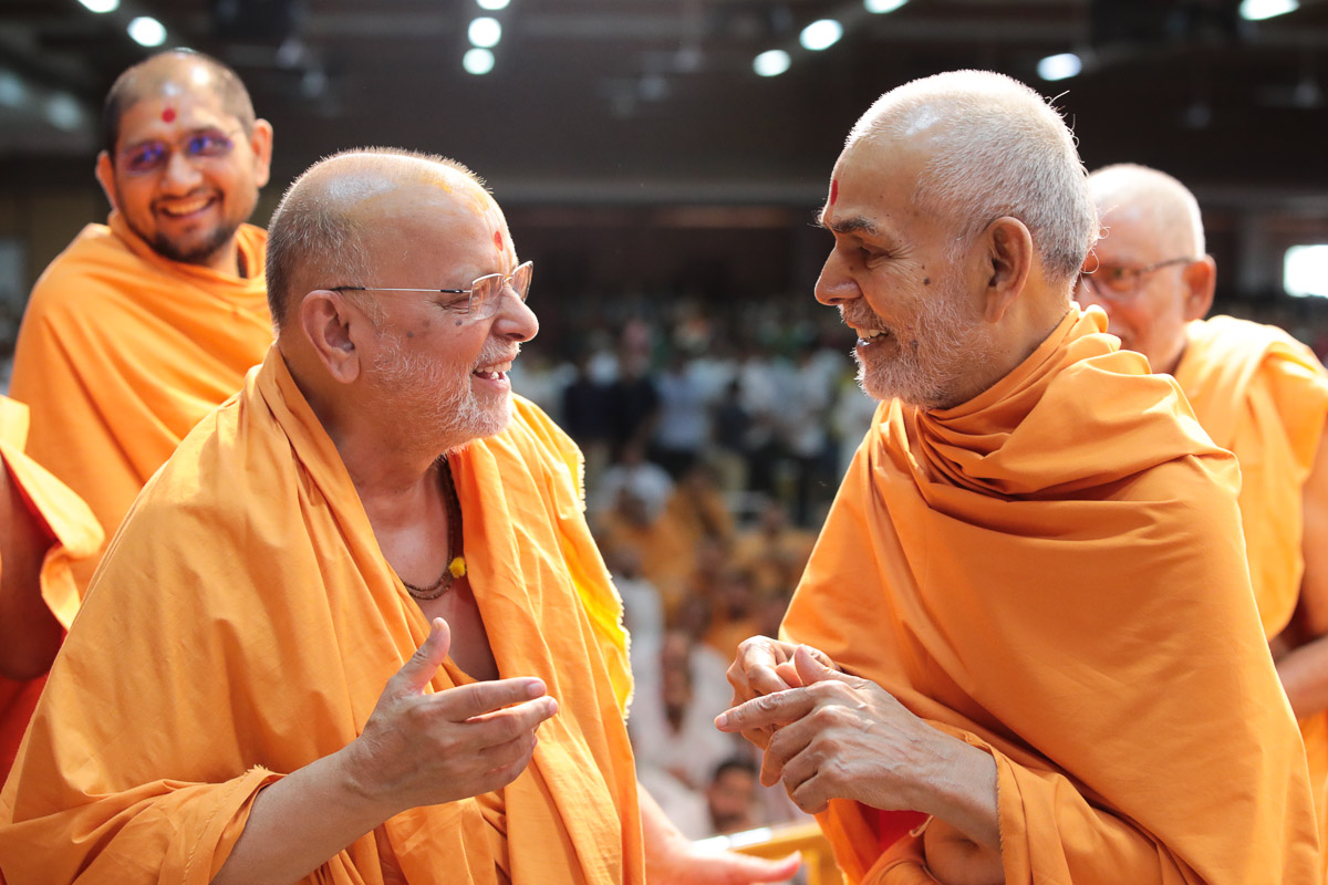 Swamishri shares a light moment with Pujya Ishwarcharan Swami