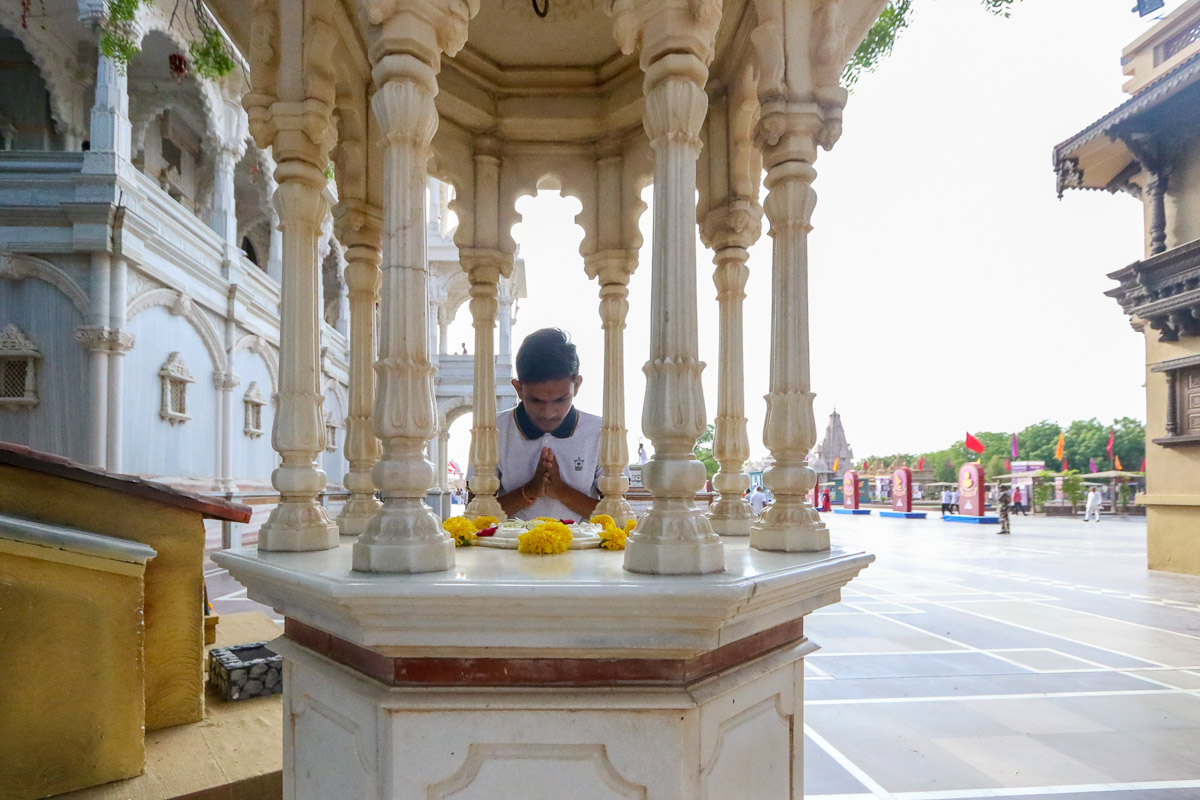 A youth doing darshan of the holy charanarvind of Bhagwan Swaminarayan