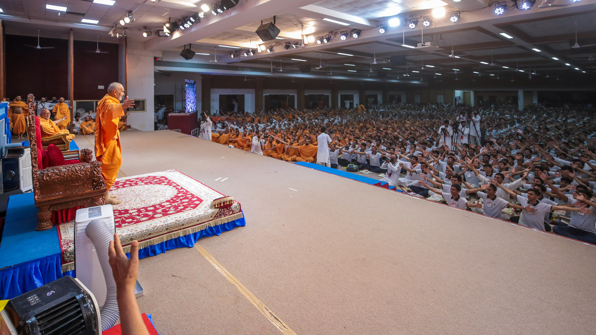 Swamishri and youths gesture to embrace each other