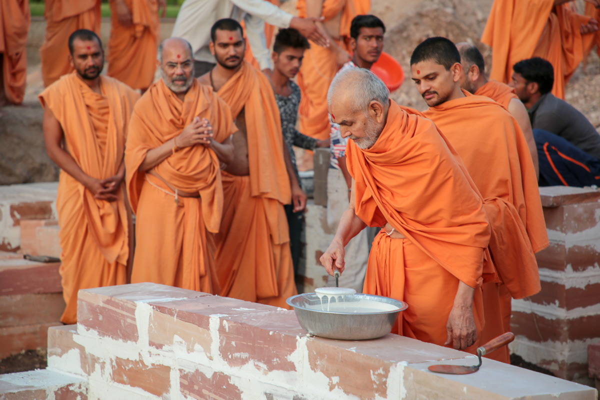 Swamishri applies cement mixture in joints of stones