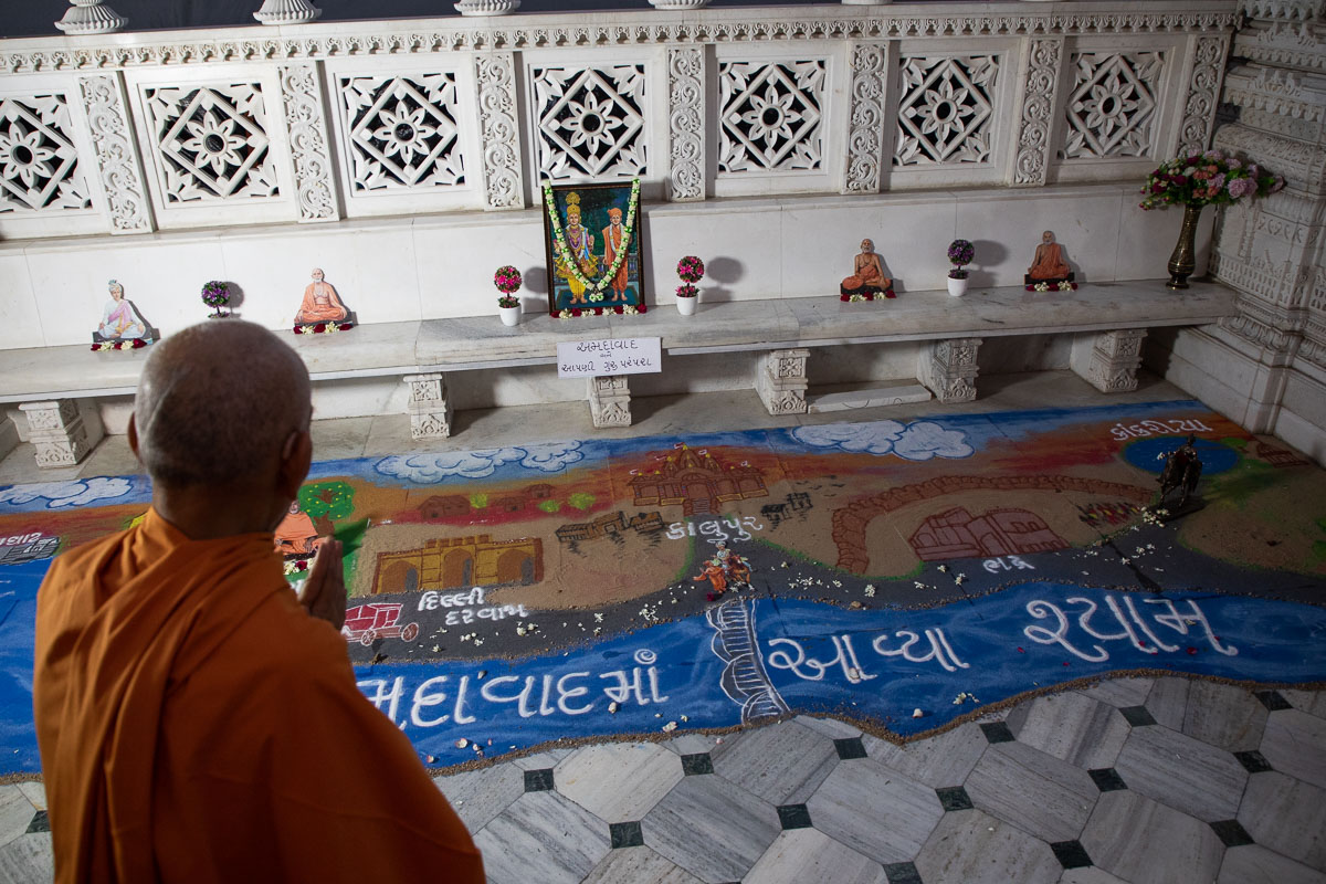 Swamishri observes a rangoli depicting the history of the Swaminarayan Sampradaya in Ahmedabad