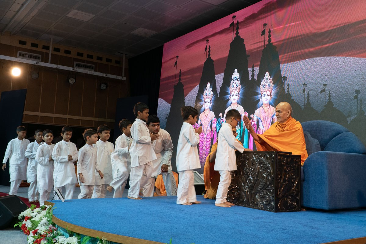 Swamishri blesses the children who recited scriptural passages during his puja