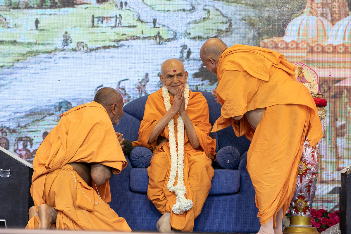 Pujya Ishwarcharan Swami and Atmakirti Swami honor Swamishri with a garland
