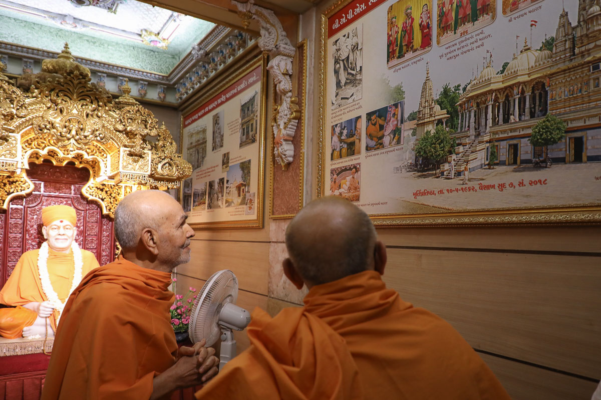 Swamishri and Pujya Ishwarcharan Swami observe one of the exhibition panels in the abhishek mandap