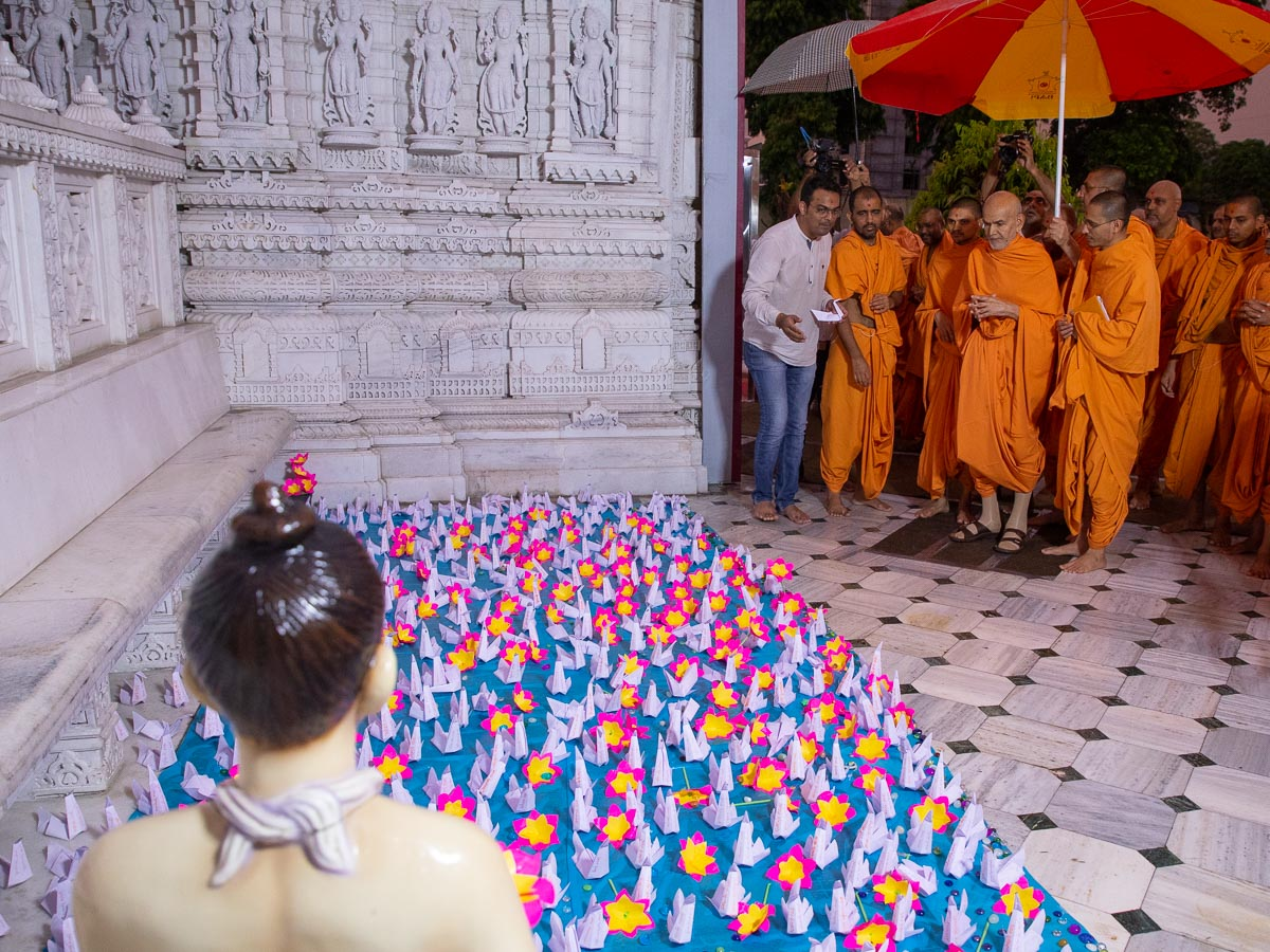 Swamishri observes a display of origami swans in the presence of Shri Nilkanth Varni at Mansarovar