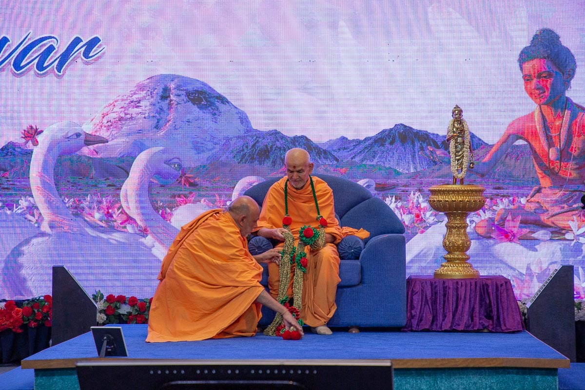 Shrijiswarup Swami honors Swamishri with a garland