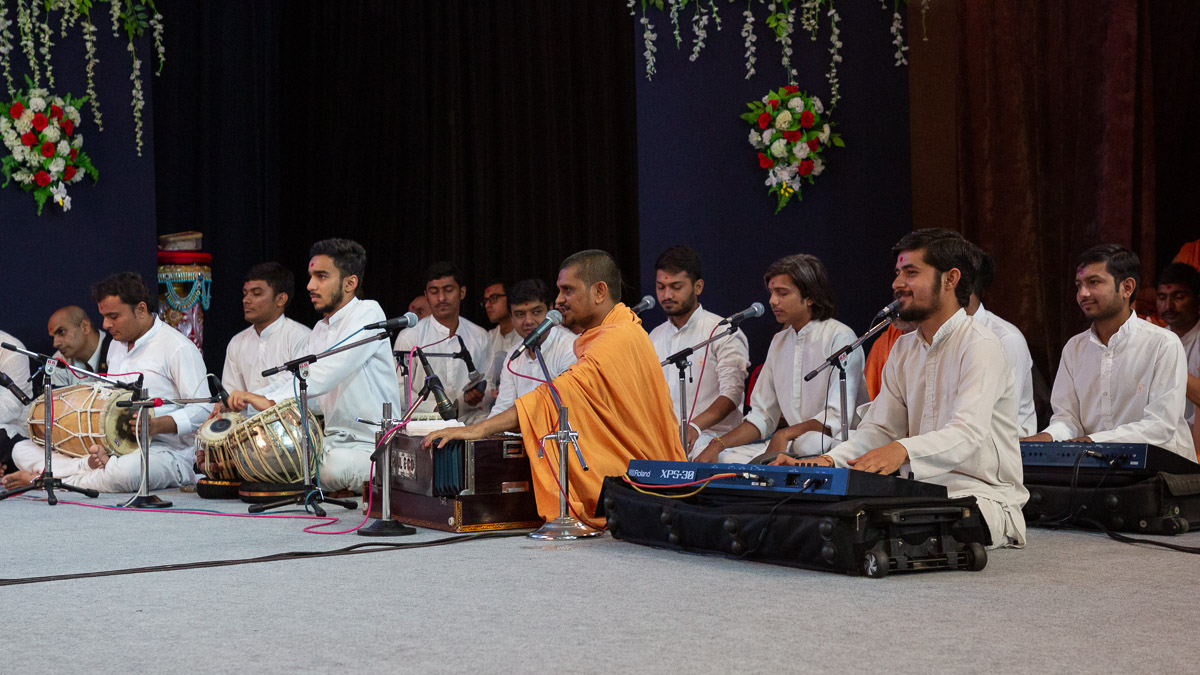 Sadhus and youths sing kirtans in Swamishri's puja