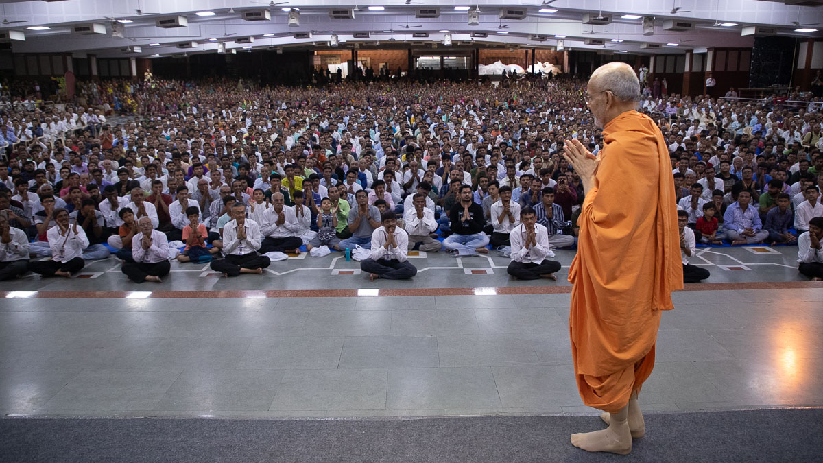 Swamishri greets all with folded hands in the Pramukh Swami Auditorium