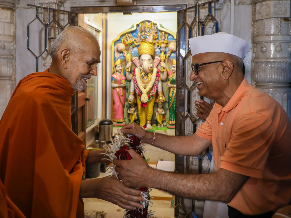 A devotee honors Swamishri with a garland