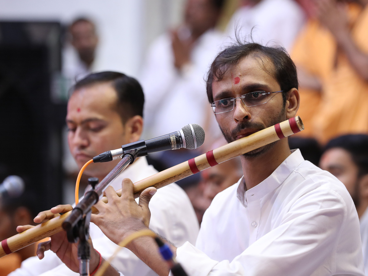 A youth plays the flute in Swamishri's puja