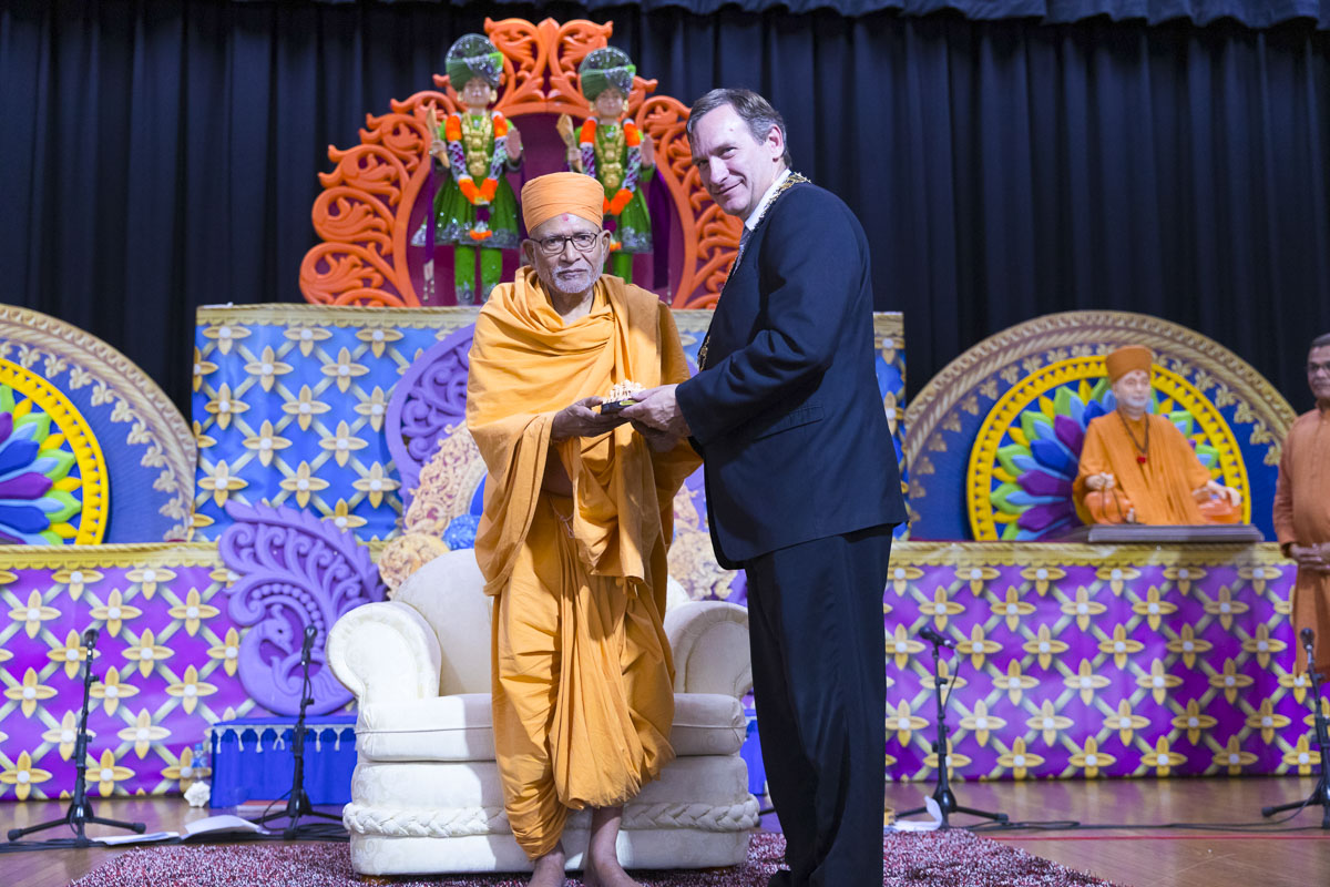 Pujya Kothari Swami presents a memento to an invited guest