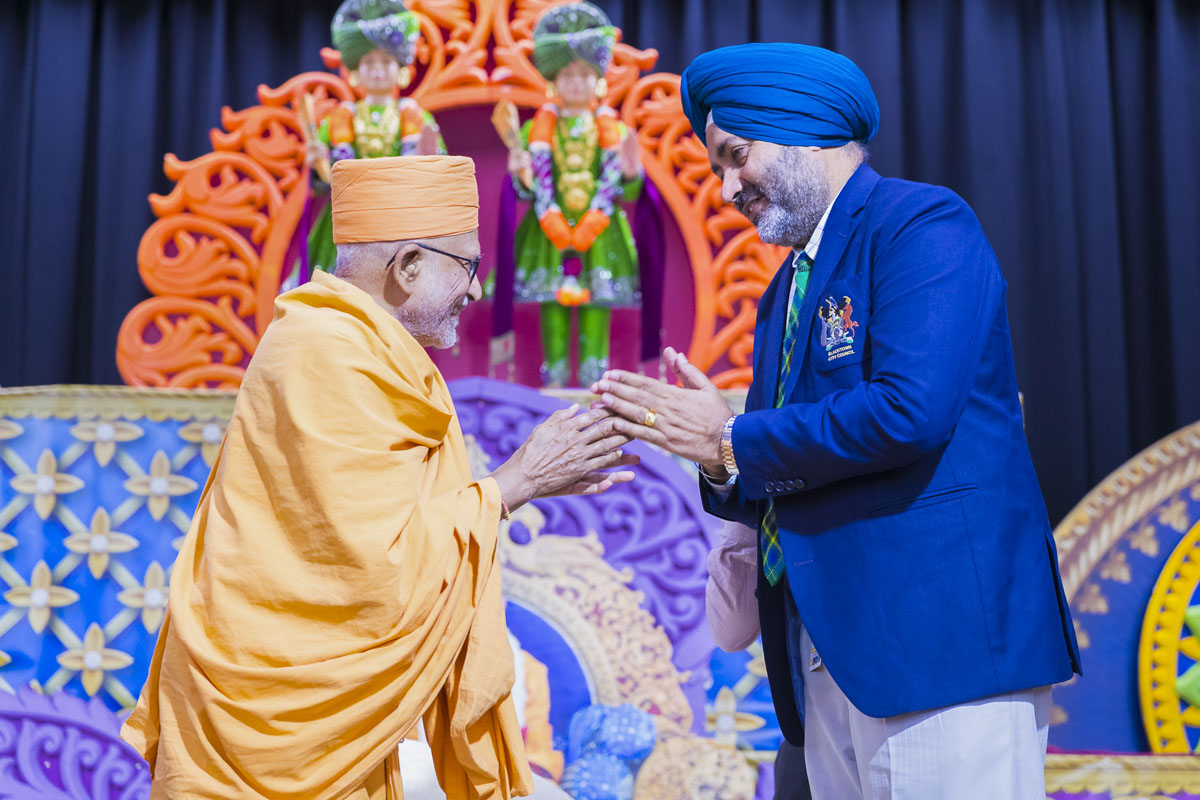 Pujya Kothari Swami greets an invited guest with 'Jai Swaminarayan'