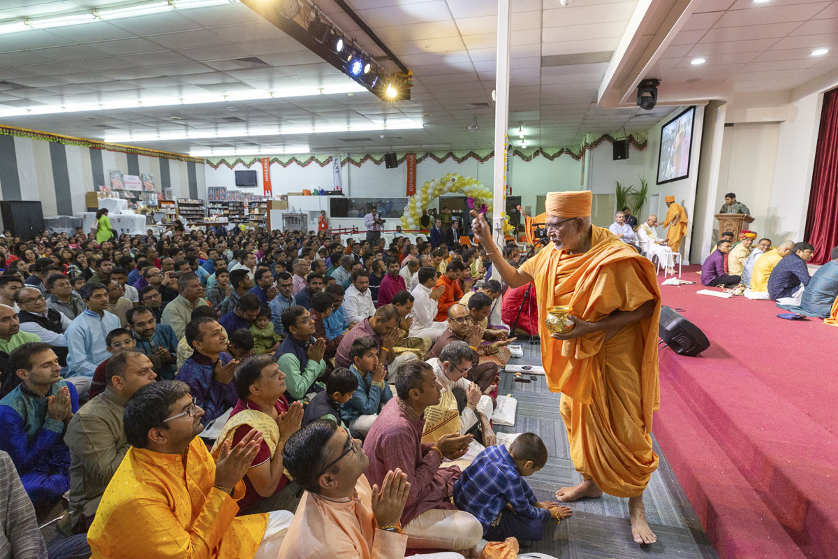 Pujya Kothari Swami showers akshat (rice grains) on devotees
