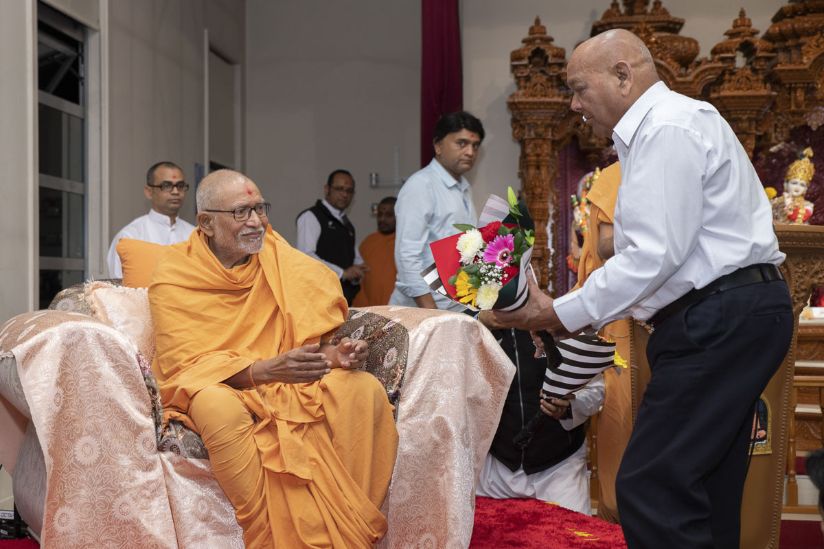 A devotee welcomes Pujya Kothari Swami with a bouquet of flowers