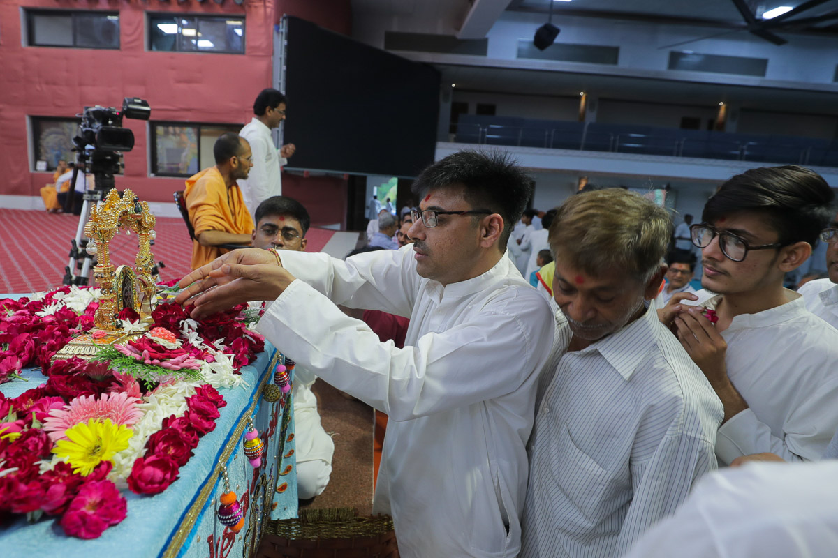 Devotees offers flowers to Shri Harikrishna Maharaj