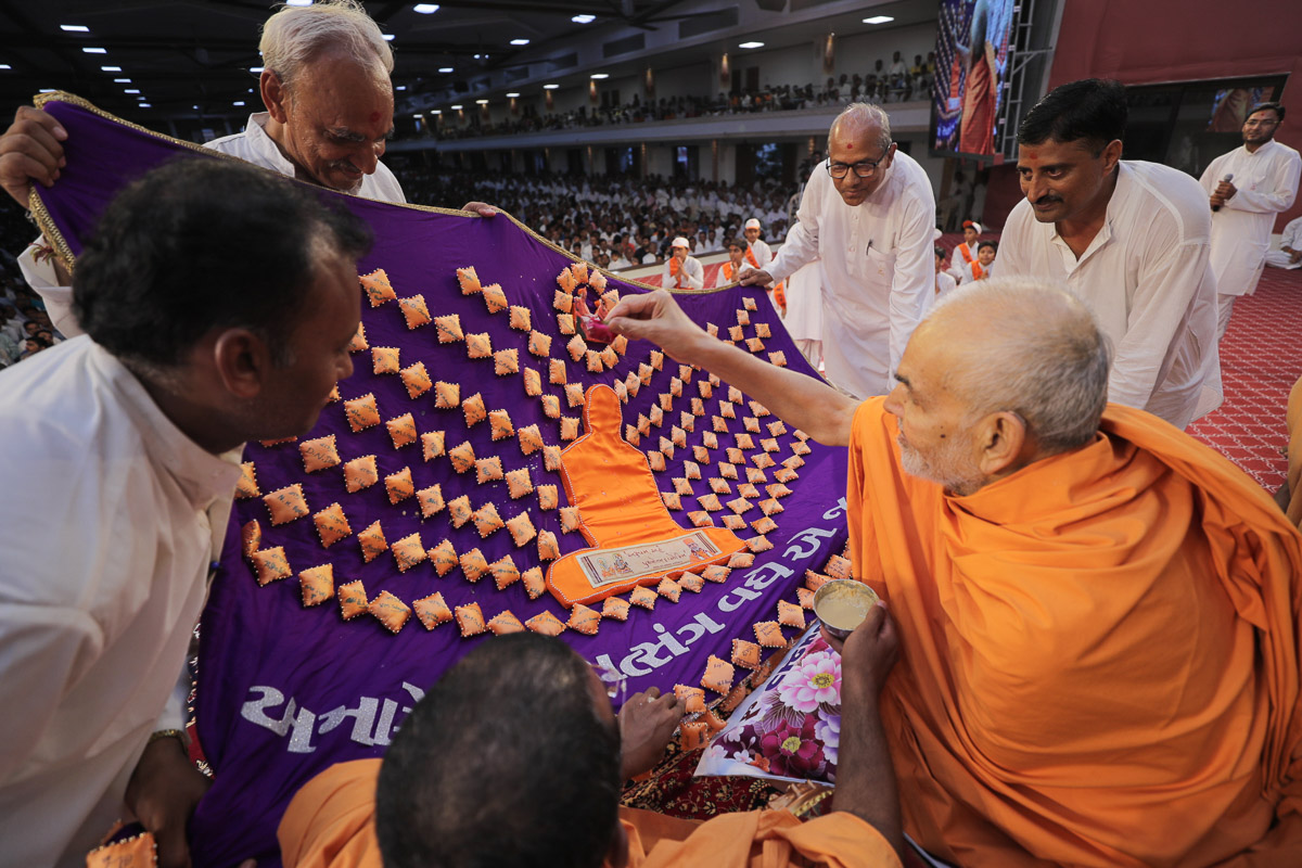 Swamishri sanctifies a shawl