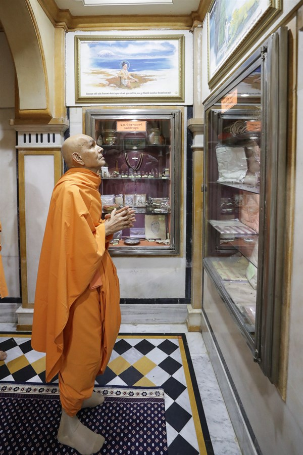 Swamishri observes a photo in the rang mandap