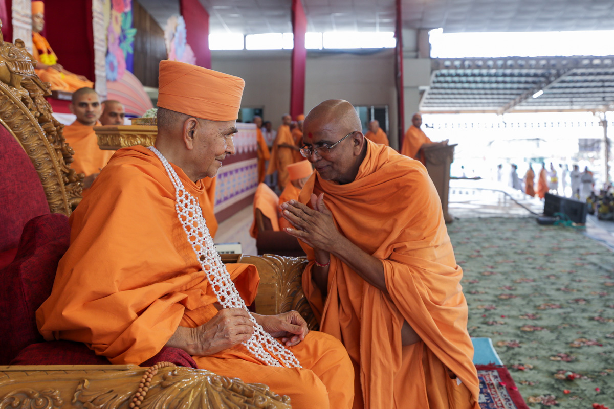 Vedagna Swami honors Swamishri with a garland