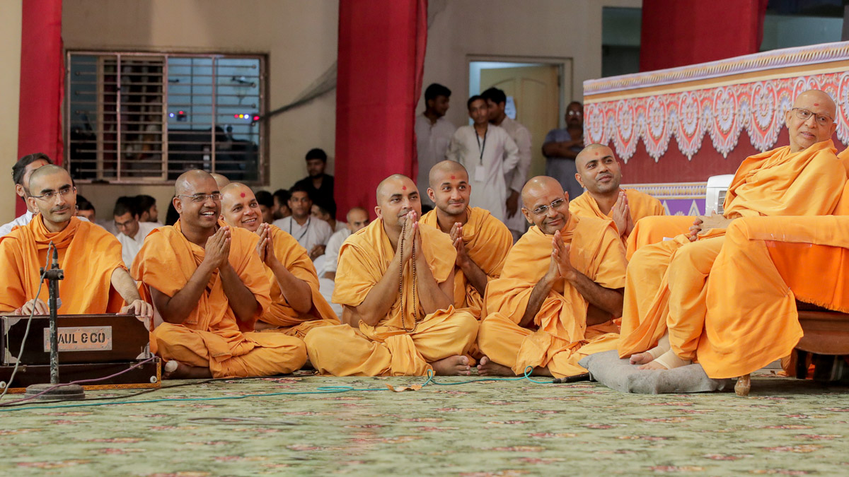 Sadhus participate in a kirtan singing game