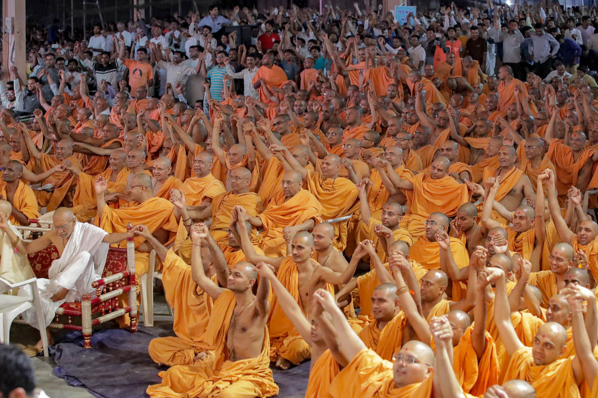 Sadhus and devotees join hands in a gesture of unity