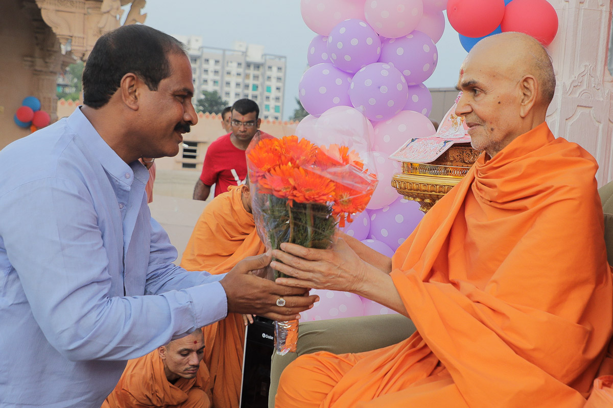 Devotees welcome Swamishri with a flower bouquet