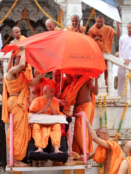 Sadhus and volunteers arrange a makeshift shelter for Swamishri against the wind and rain