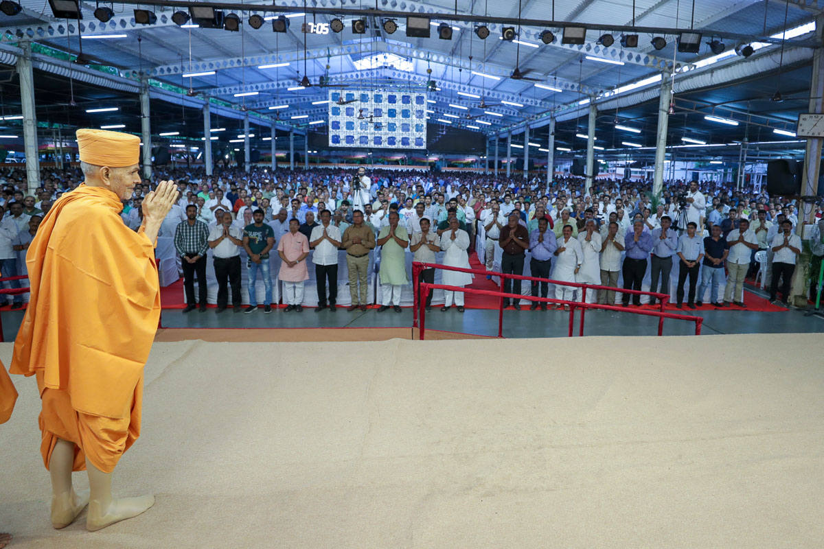 Swamishri greets all with folded hands in the evening assembly