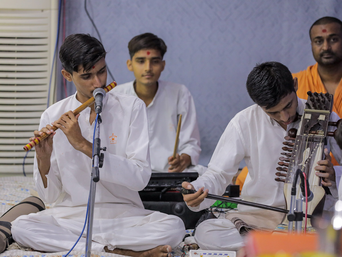 Youths play musical instruments before Swamishri