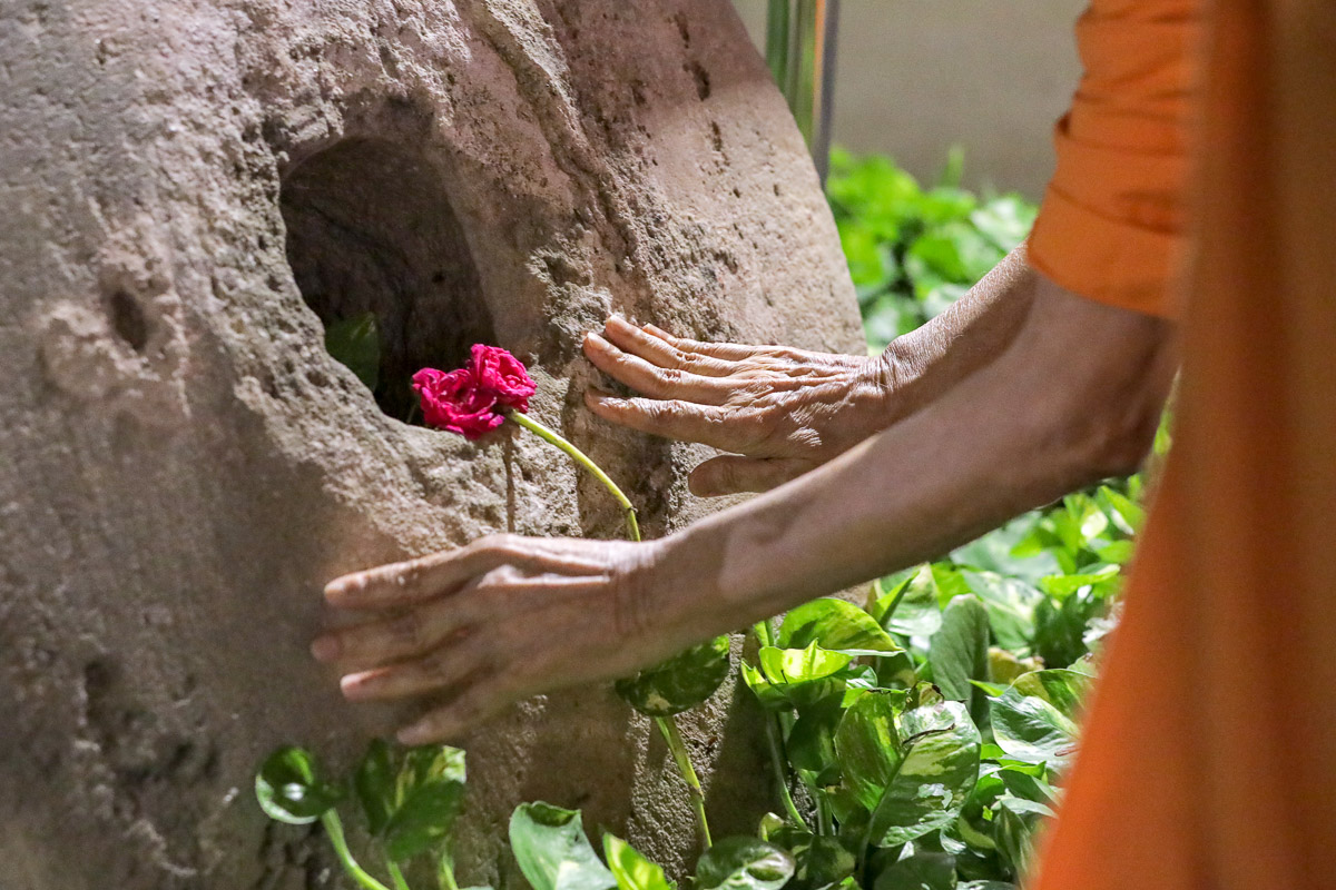 Swamishri reverentially touches a sanctified stone used by Brahmaswarup Pramukh Swami Maharaj to prepare limestone during the construction of Atladra mandir